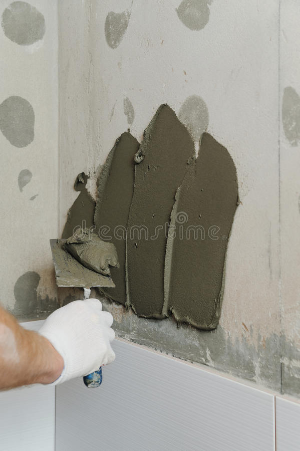 Installing the tiles on the wall. A worker putting adhesive on the wall using a trowel stock photography