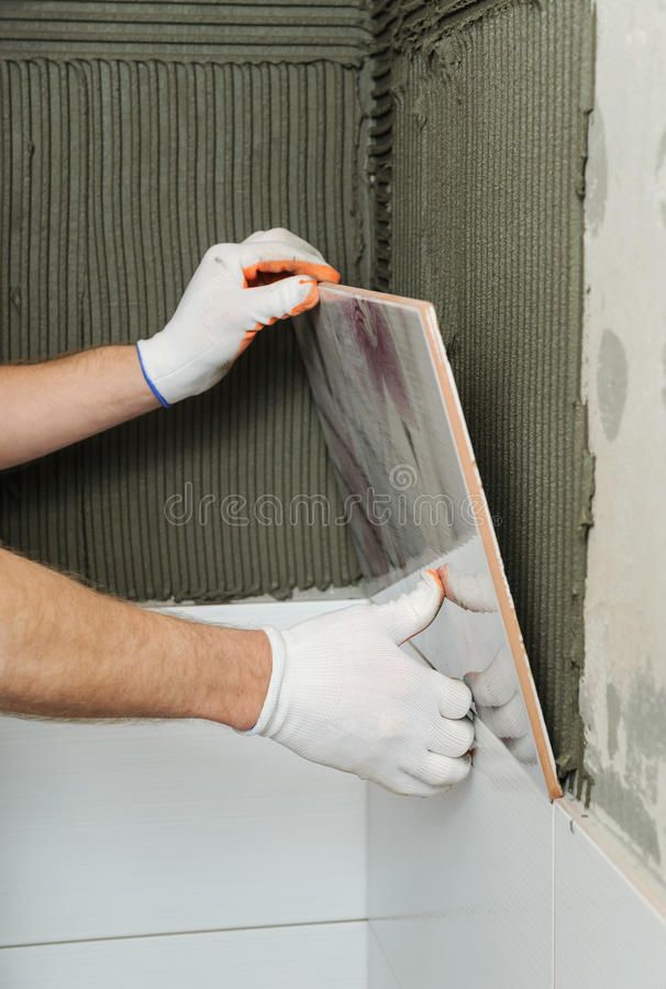Installing the tiles on the wall. A worker putting tiles in the bathroom royalty free stock image