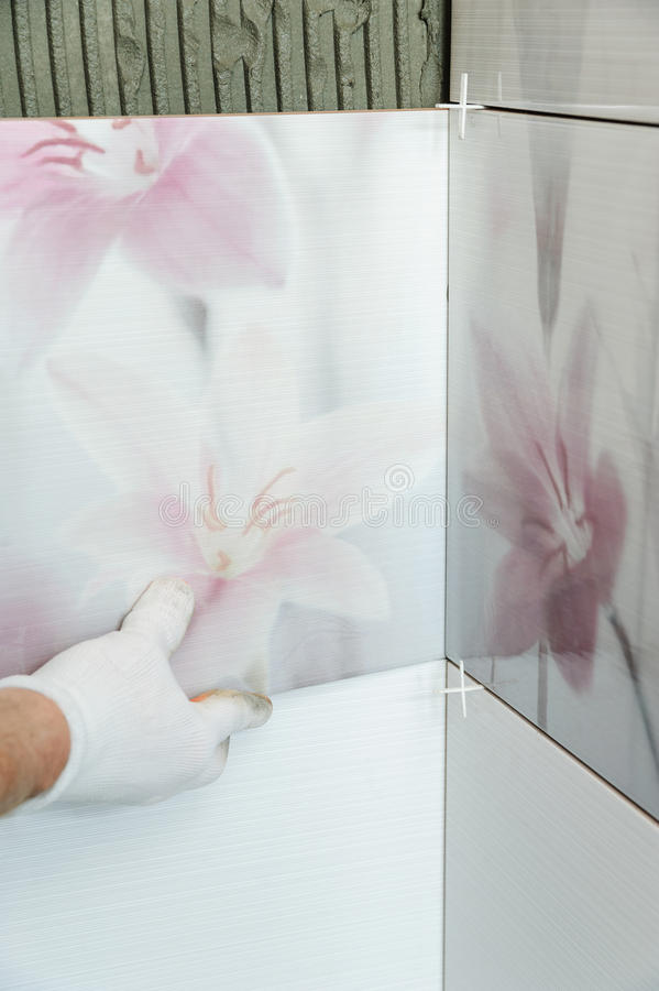 Installing the tiles on the wall. A worker putting tiles in the bathroom stock images