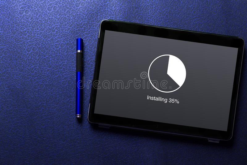 Installing update with circle load percentage waiting indicator concept on tablet screen with blue pen on blue pattern. Textured background royalty free stock image