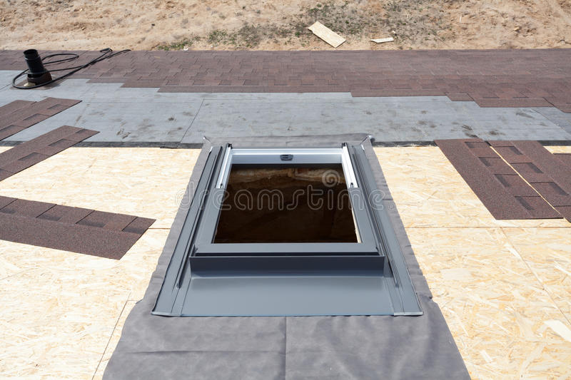 Installing window skylight on a roof with Asphalt Shingles or Bitumen Tiles under construction. royalty free stock photography