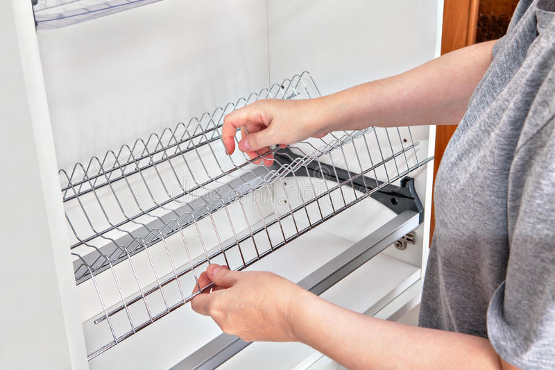 Installing wire dish rack for drying dishes inside kitchen cabin. Assembling wall mounted shelf under kitchen cupboard with inside plate rack with drip tray stock photo