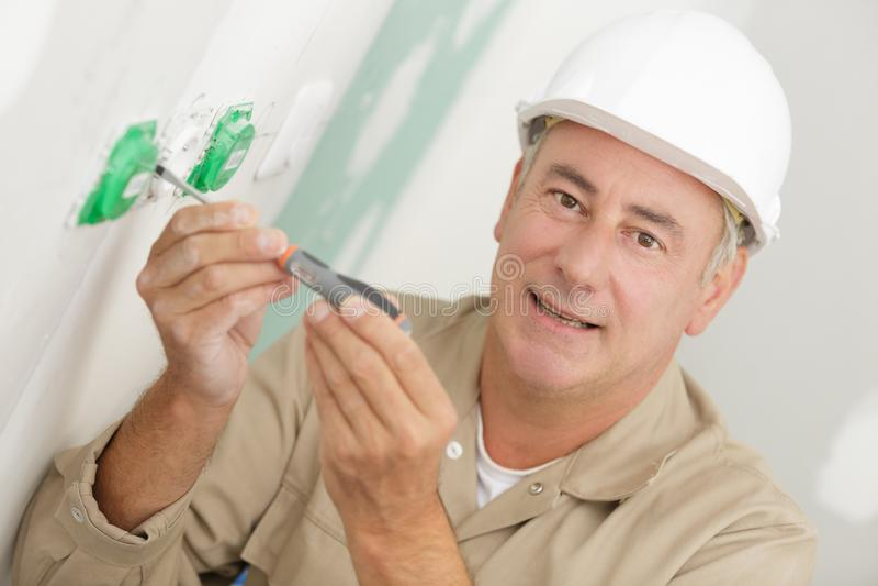 Installling Schalter und Sockel des Elektrikers stockbild