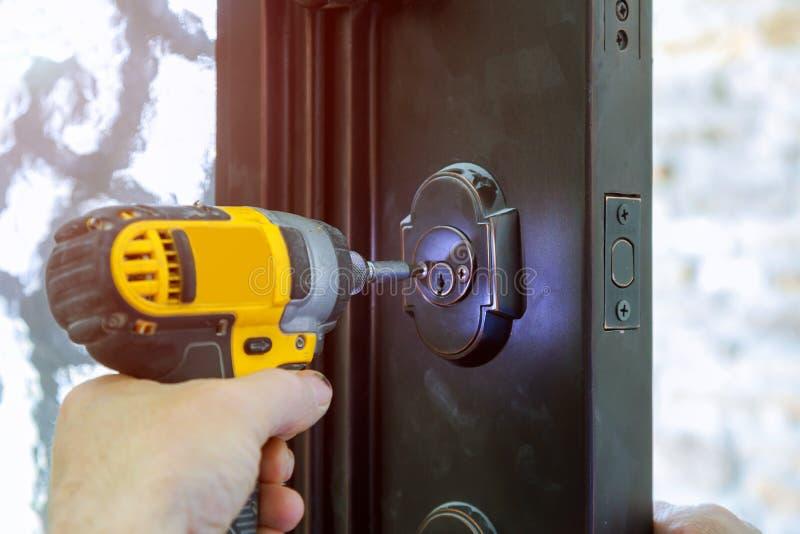 Instaluje drzwiową rękojeść z kędziorkiem, cieśla śruba, używać świderu śrubokręt, zakończenie zdjęcia royalty free