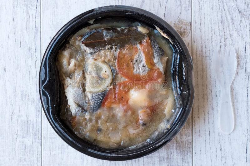 Instand Seafood Gilt-Head Sea Bream Fish in Plastic Container with Fork / Steamed Fish Stew. stock photography
