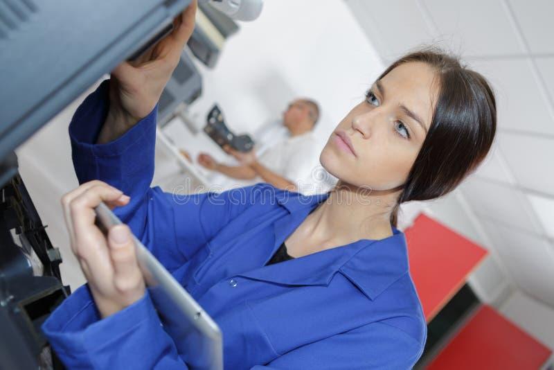 Instandhaltungsdrucker des weiblichen Technikers unter Verwendung des Tablet-Computers stockbild