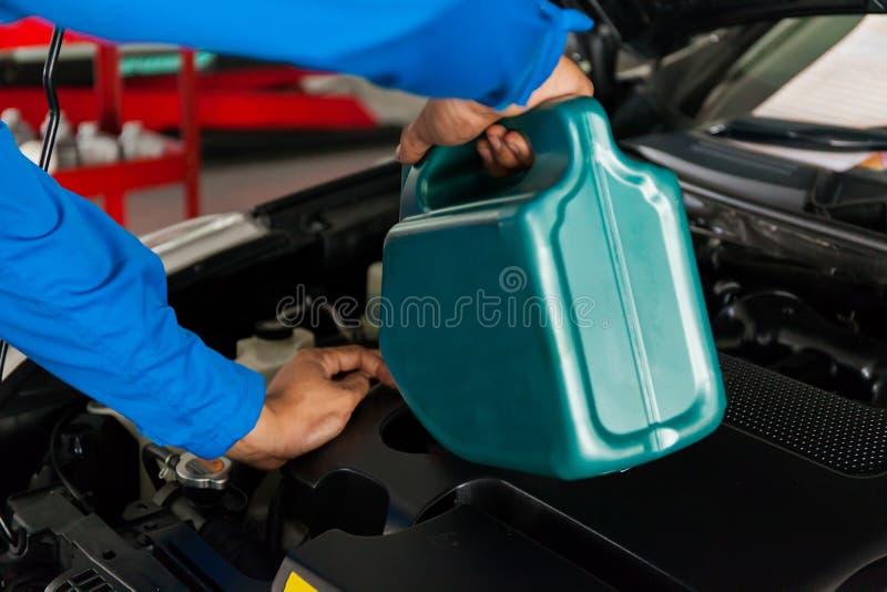Instandhaltungsmechaniker, der neues Ölschmiermittel in den Automotor gießt stockbild
