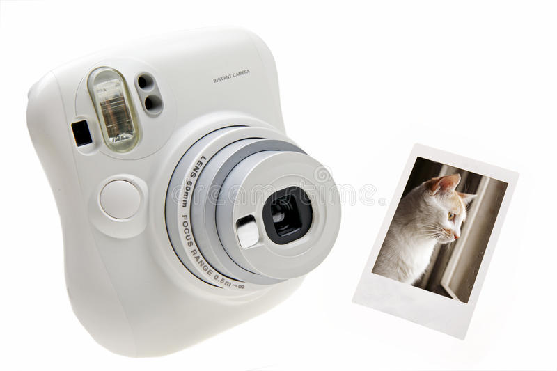 Instant camera. An instant camera with a photo isolated on white stock images