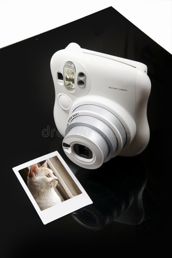 Instant camera. An instant camera with a photo on black-white background royalty free stock photos