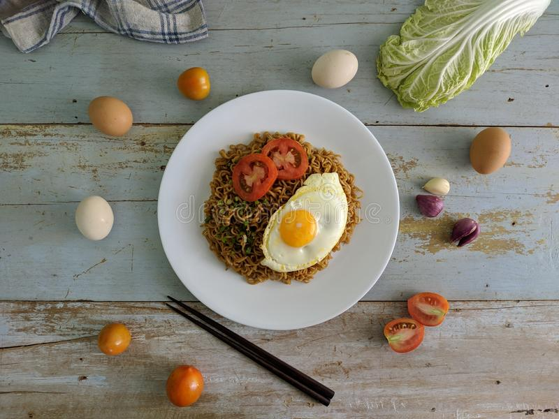Fried noodles served with fried egg. Food flat lay concept. From top view on wood background stock image