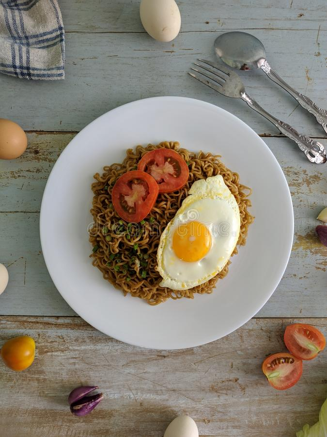 Fried noodles served with fried egg. Food flat lay concept. From top view on wood background royalty free stock photos