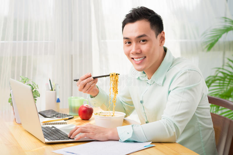 young man eating instant noodles while working with laptop