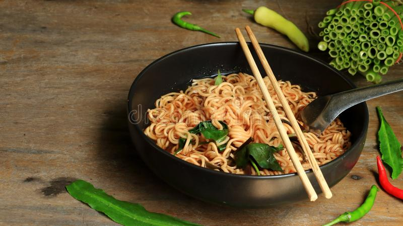 Instant noodles and vegetables in a black cup on a wooden background stock image