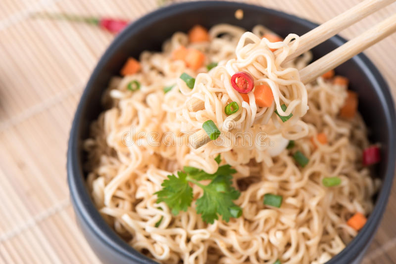 Instant noodles with vegetables on chopstick. Closed up instant noodles with vegetables on chopstick, junk food or fast food concept stock photos