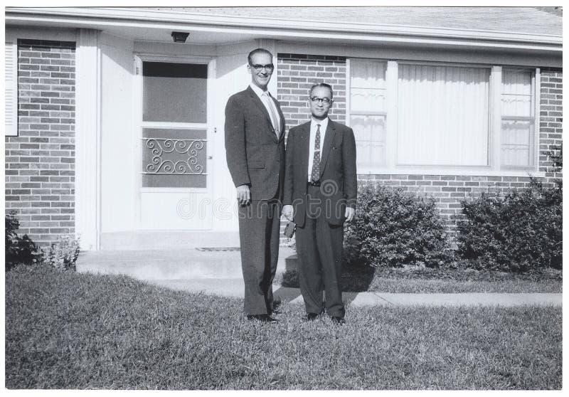 Instantané de vintage : Homme grand de short d'homme en dehors de maison surburban image libre de droits