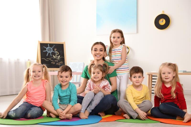 Institutrice gardienne avec le groupe d'enfants dans la salle de jeux images libres de droits