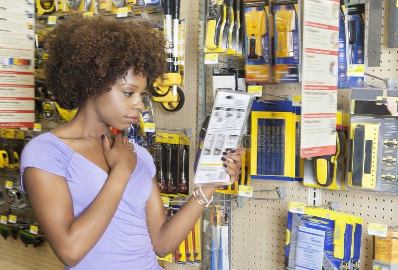 Instruções afro-americanos da leitura da mulher em um produto no mercado super foto de stock royalty free
