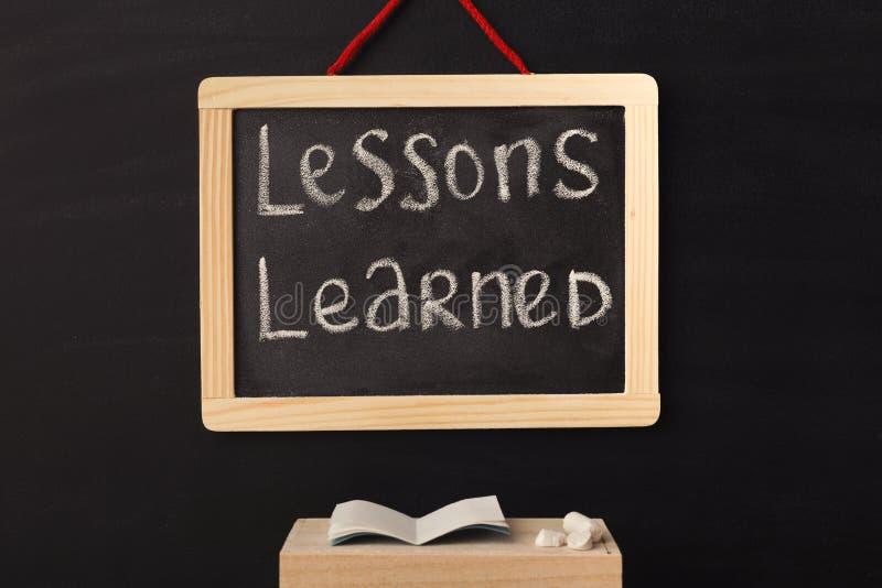 Instruído de lições da palavra escrito no quadro diminuto fotografia de stock