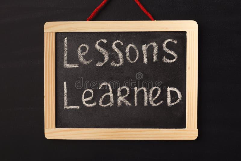 Instruído de lições da palavra escrito no quadro diminuto foto de stock