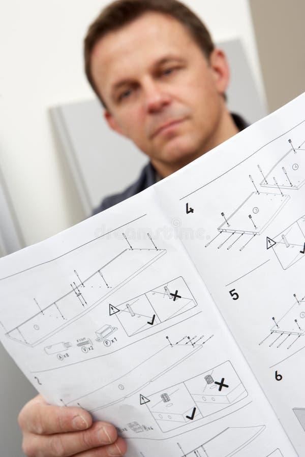 Instrucciones de asamblea de la lectura del hombre para el paquete plano imagen de archivo