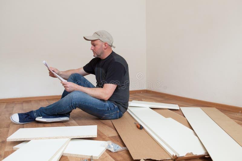 Instrucciones de montaje de la lectura del hombre para los muebles en nueva casa Reparaci?n del carpintero y muebles de junta en  imágenes de archivo libres de regalías