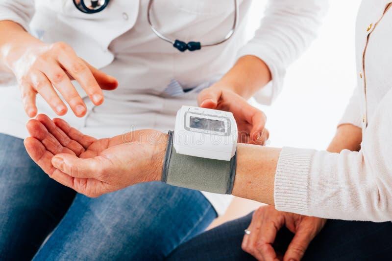 Instrucciones del givind del doctor sobre el tensiómetro imagen de archivo