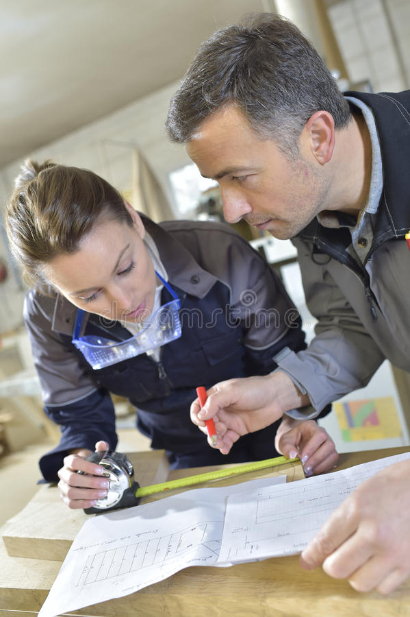 Instrucotr and carpenter trainee stock image
