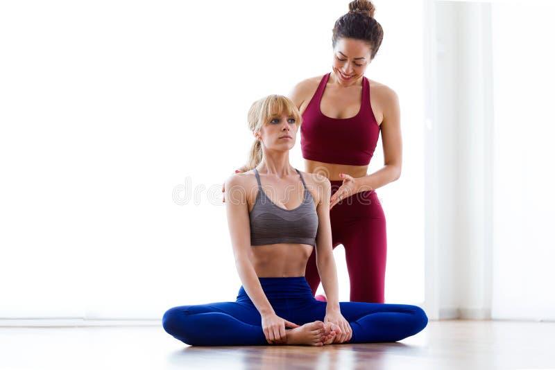 Instructeur assez jeune de yoga aidant son étudiant en session de yoga à la maison Pose de Baddha Konasana images libres de droits
