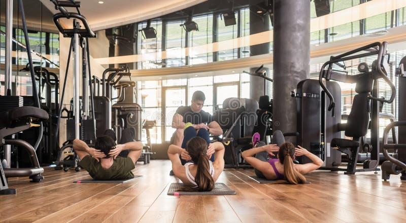 Instructeur de forme physique chronométrant l'exercice latéral de craquement avec les jambes augmentées image libre de droits