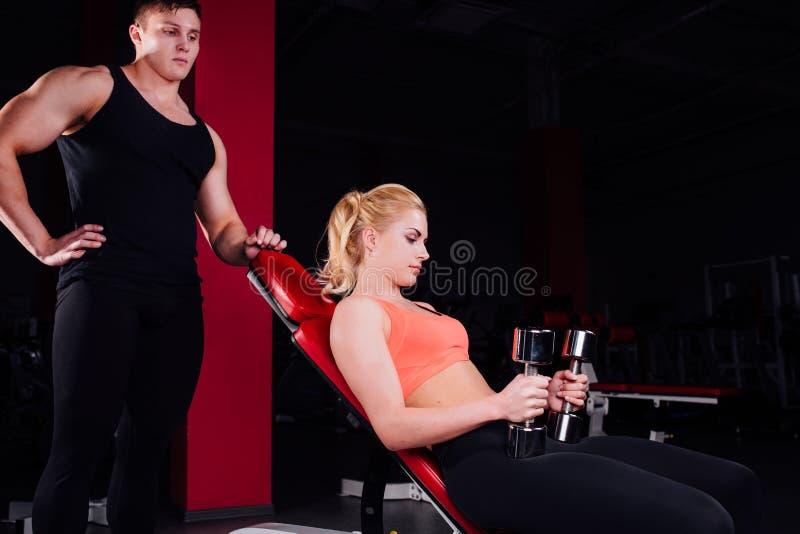 Instructeur de forme physique s'exerçant avec son client au gymnase photographie stock