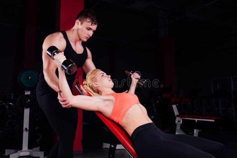 Instructeur de forme physique s'exerçant avec son client au gymnase photos stock
