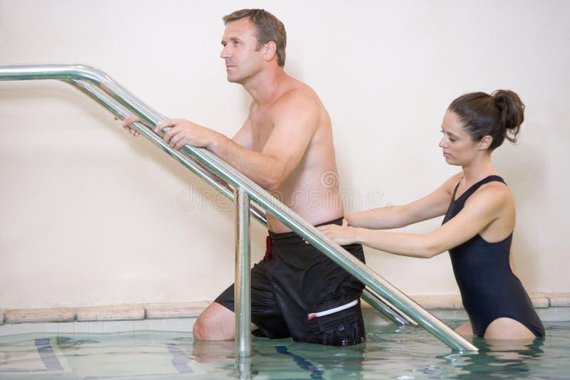 Instructeur en Patiënt die de Therapie van het Water ondergaan stock foto