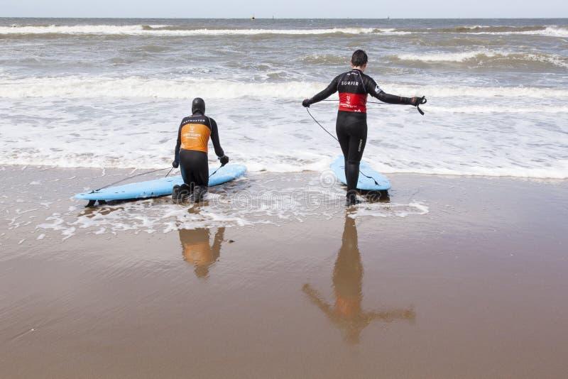 Instructeur en surfer op het strand van Scheveningen stock afbeeldingen
