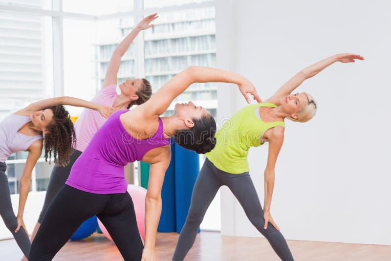 Instructeur en vrouwelijke vrienden die uitrekkende oefening doen stock foto