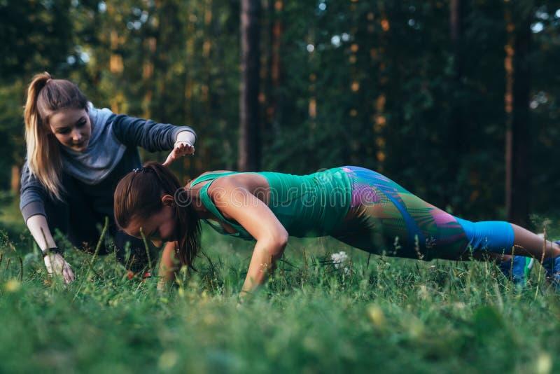 Instructeur féminin de forme physique aidant la jeune femme faisant l'exercice de pompe sur l'herbe en parc image stock