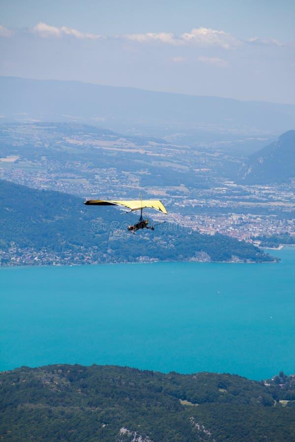 Instructeur Flying de deltaplane dans le deltaplane avec le client au-dessus du lac annecy par le paysage et les villes de montag images stock