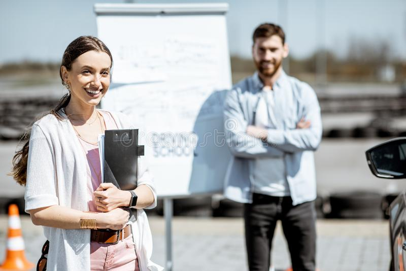 Instructeur met vrouwelijke student op de school van de bestuurder stock foto