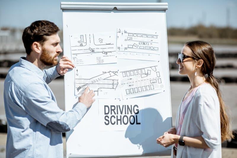 Instructeur montrant des shemes du trafic aux outdooors d'une étudiante photographie stock libre de droits