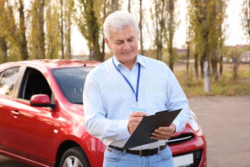 Instructeur supérieur avec le presse-papiers près de la voiture dehors Obtenez le permis photo stock