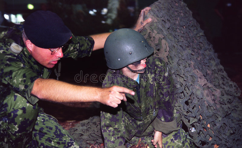 Instructing child soldier stock images