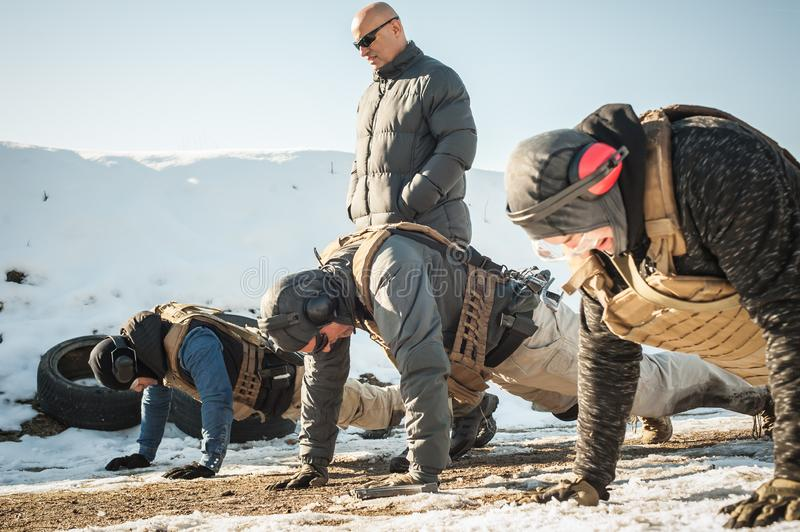 Instructor and army soldiers have hard training and doing push-ups. Instructor and army soldiers in complete equipment have hard training and doing push-ups on royalty free stock photography