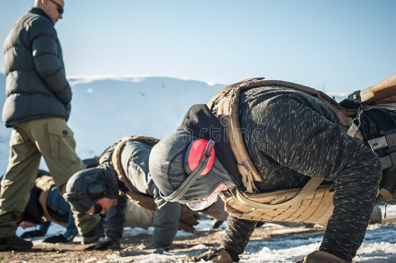 Instructor and army soldiers have hard training and doing push-ups. Instructor and army soldiers in complete equipment have hard training and doing push-ups on stock image