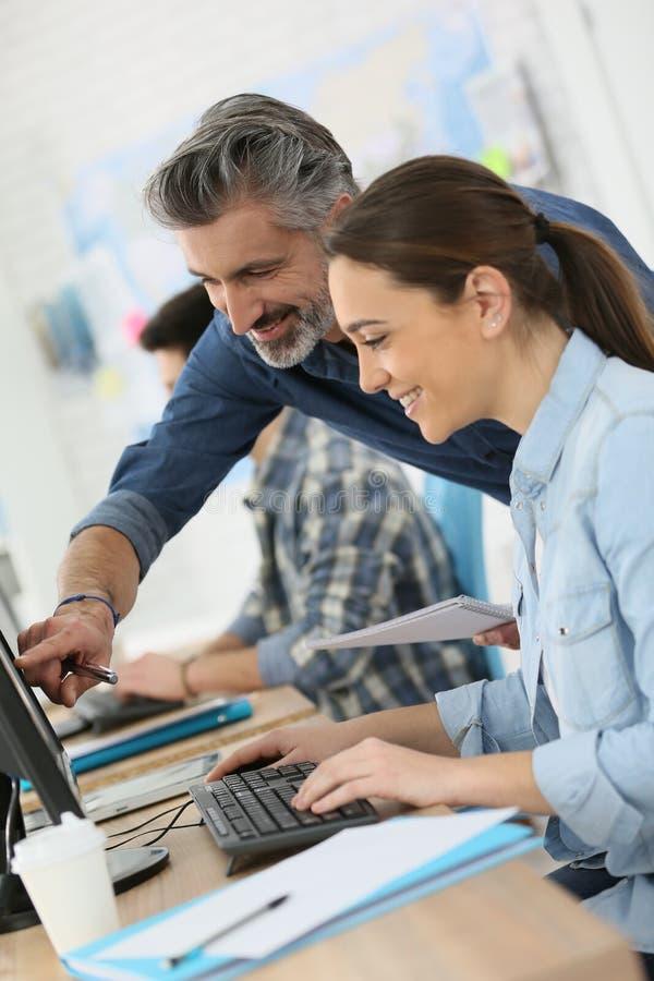 Instructor con el aprendiz que trabaja en el ordenador imagen de archivo libre de regalías