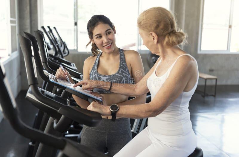 Instructor con la mujer mayor que ejercita la bici de giro en gimnasio de la aptitud concepto sano mayor de la forma de vida fotos de archivo