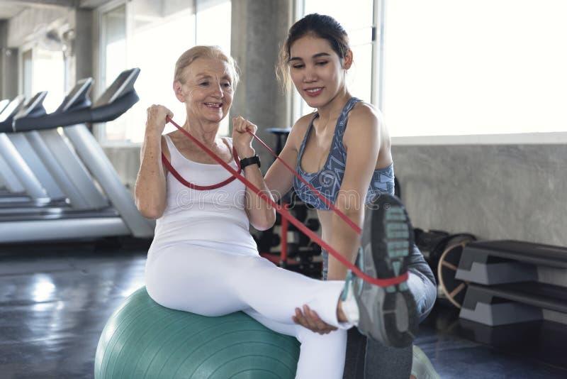 Instructor con la mujer mayor que estira ejercicio en gimnasio forma de vida y concepto sanos mayores del entrenamiento fotos de archivo