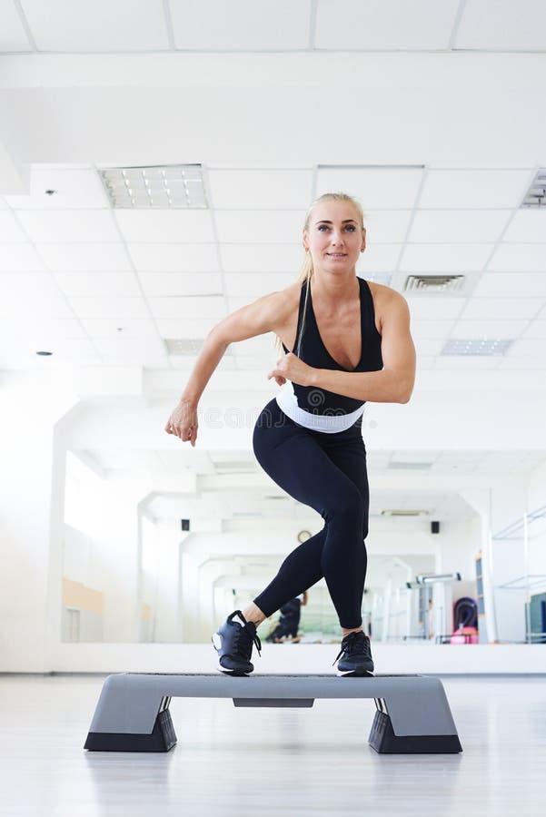 Instructor concentrado que hace aeróbicos en un gimnasio foto de archivo libre de regalías