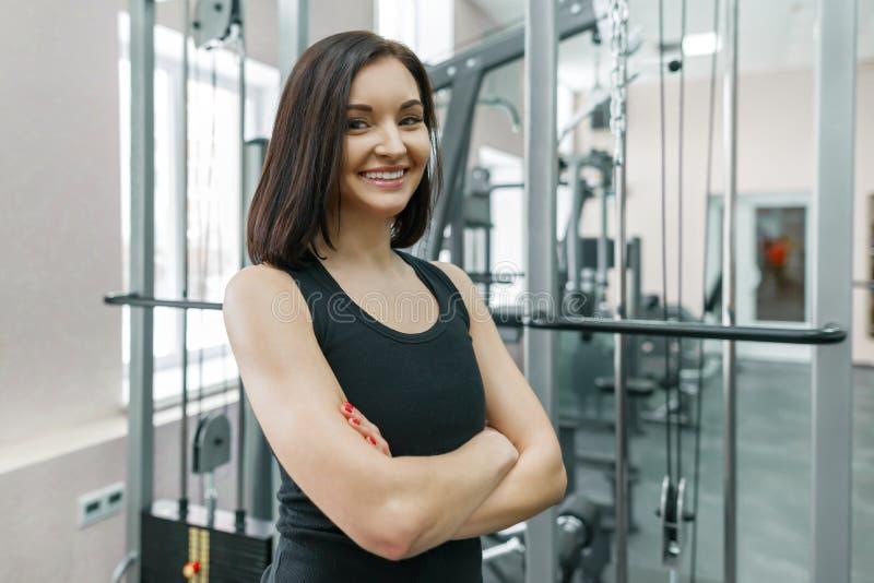 Instructor confiado atlético joven de la aptitud de la mujer que presenta en gimnasio con los brazos cruzados doblados, mirando i imagen de archivo libre de regalías