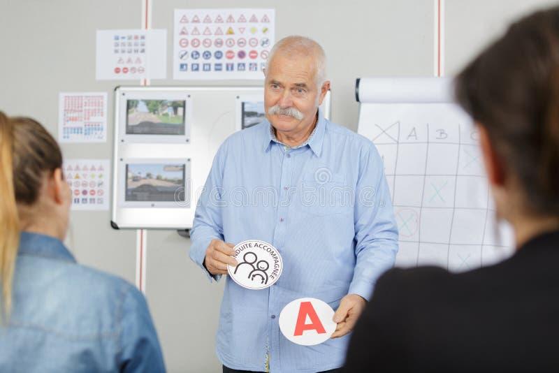 Instructor de conducción mayor hermoso en clase imagen de archivo libre de regalías