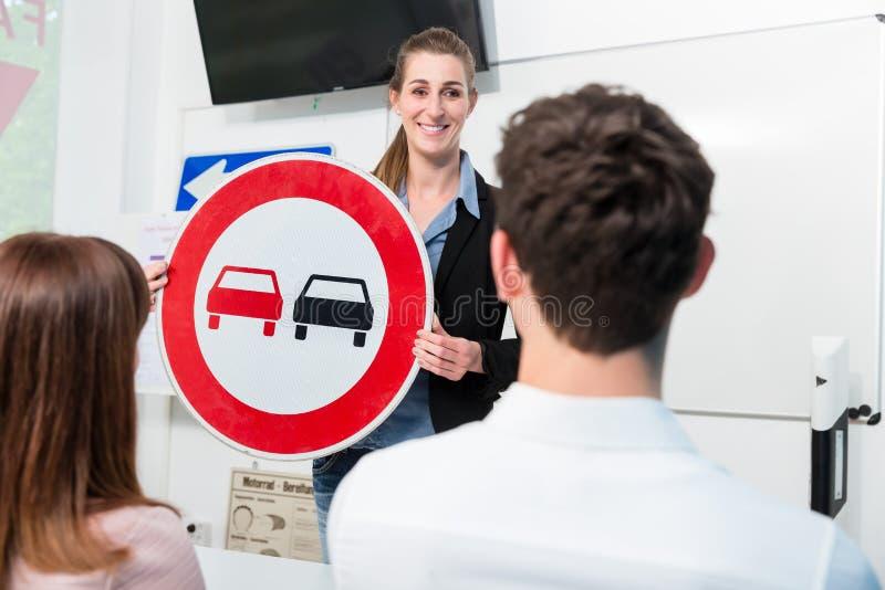 Instructor de conducción que explica el significado de la placa de calle de clasificar imágenes de archivo libres de regalías