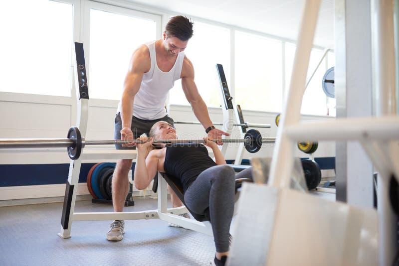 Instructor de gimnasio Supporting Woman en Barbell de elevación foto de archivo